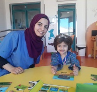 The story-teller Samah plays with 3-year-old Wafa